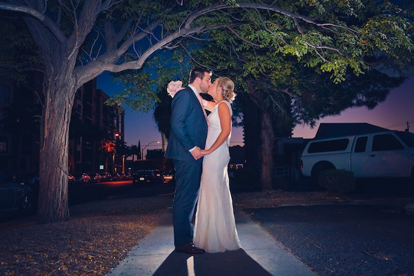 wedding couple pose outside during sunset under a beautiful tree