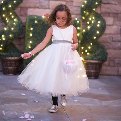 Flower girl sprinkling rose petals