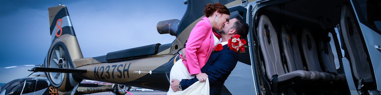 Groom embraces his wife in front of the helicopter wedding in Vegas.