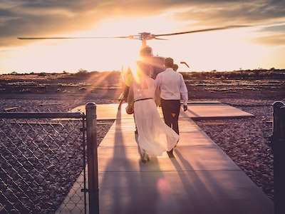 Wedding couple strolls in to the sunset to get to their helicopter - Ascend Package