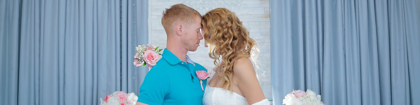 Newlyweds romantically touch foreheads in their gorgeously lit wedding chapel
