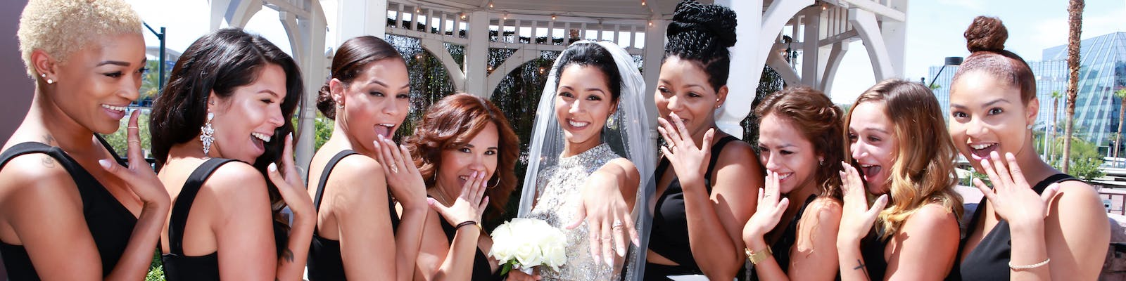 Bride shows off her ring as her bridesmaids look in awe