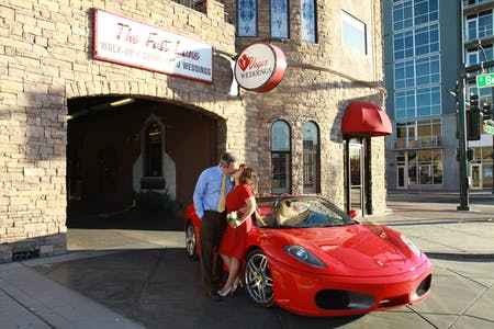 newlyweds kiss in front of the red sportscar parked in front of the fast lane newlyweds in the fast lane drive thru wedding tunnel