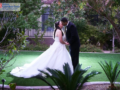 Wedding couple kisses on the green at the Hilton Hawaiian Gardens