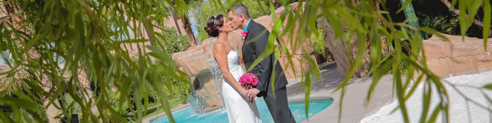 Newlyweds framed by tree leaves are kissing poolside