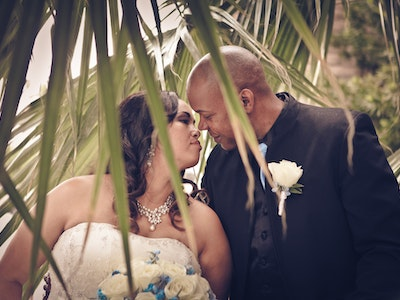 Wedding couple gets close behind the palms at their garden wedding in Vegas