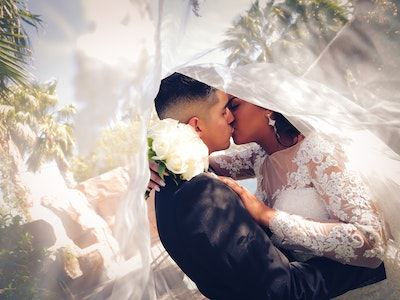 Camera peaks under the brides long veil as the newlyweds kiss