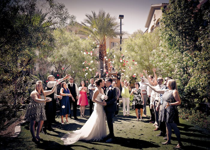 Guests circle the newlyweds and toss rose petals