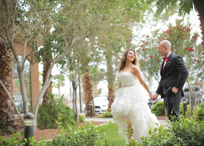 Newlyweds walk while holding hands among trees