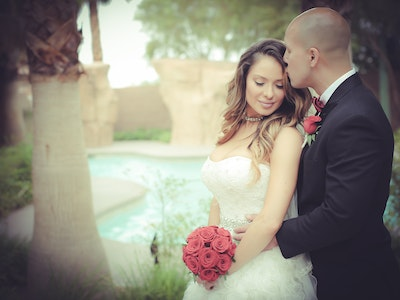 Couple poses in their outdoor wedding venue
