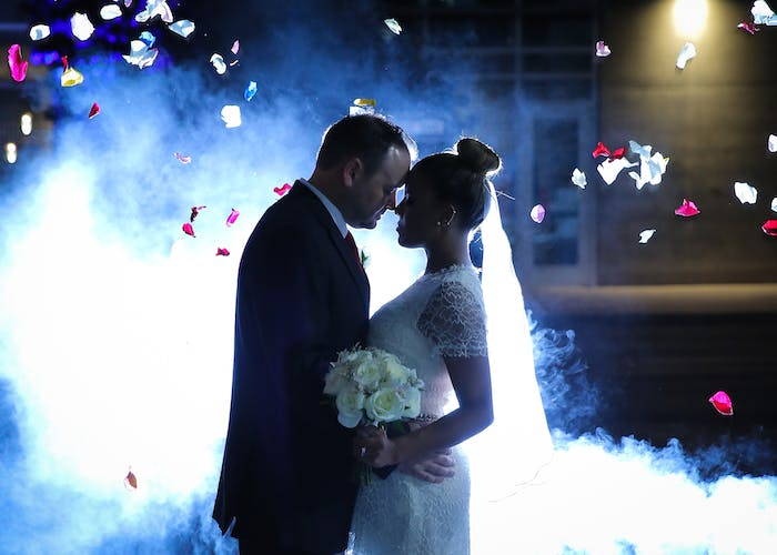 backlit newlyweds with fog and rose petals flying