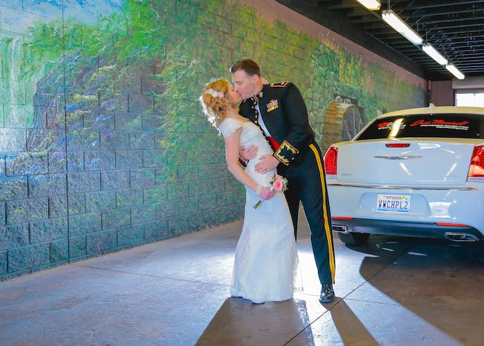 Groom dips bride for a kiss in front of their limo,