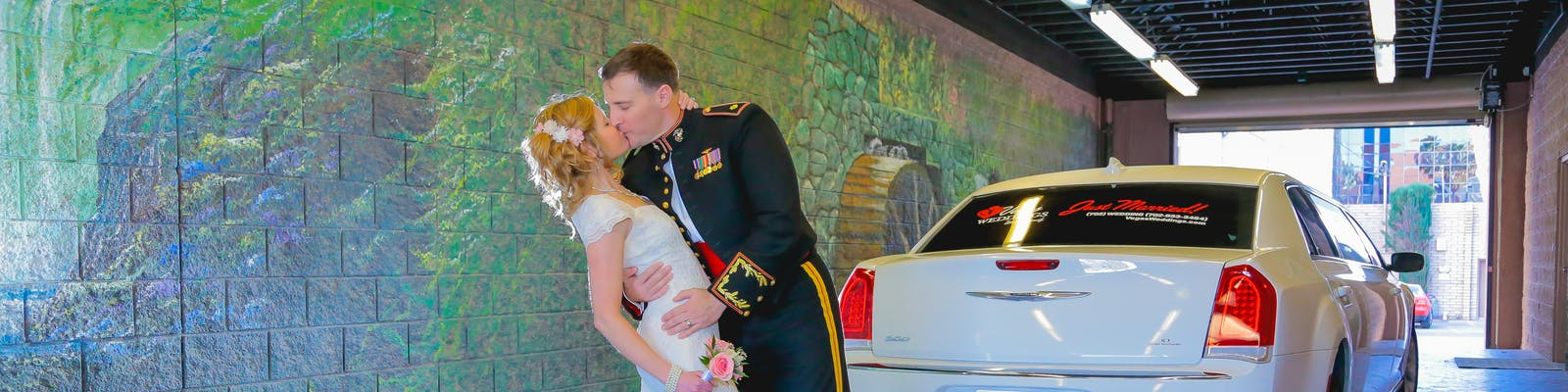 Groom dips bride for a kiss in front of the limo,