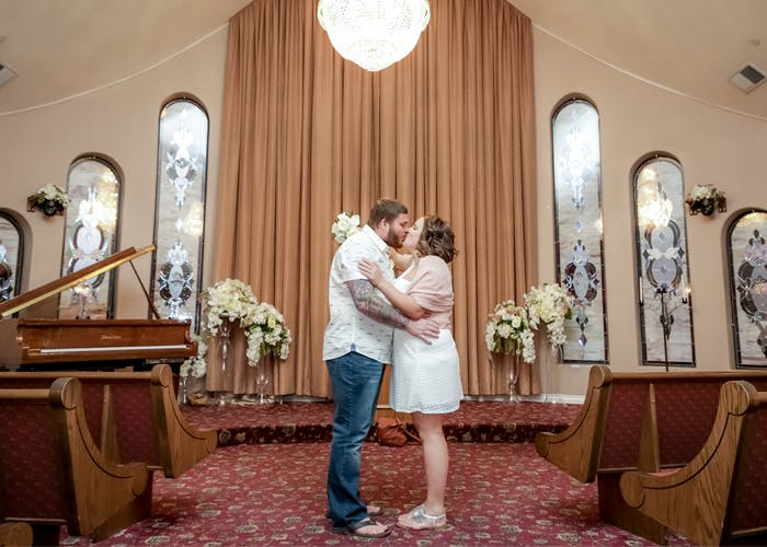 Couple kisses in their gorgeous chapel