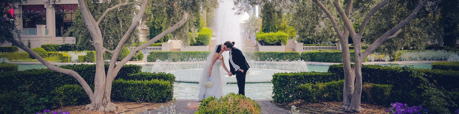 Husband and wife kissing in front of a garden fountain