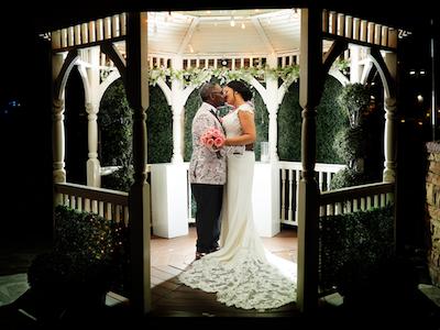 Newlyweds kiss outdoors in The Terrace Gazebo wedding chapel