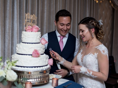 A couple with decorated wedding cake in The Reception Hall - Reception Package Graphic
